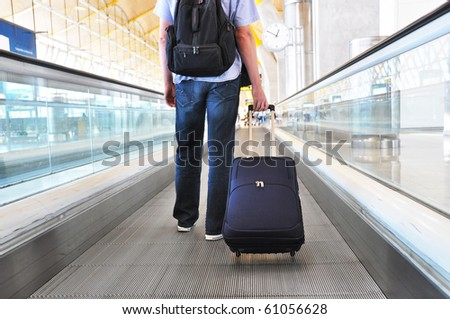 Traveler with a bag on the speedwalk - stock photo