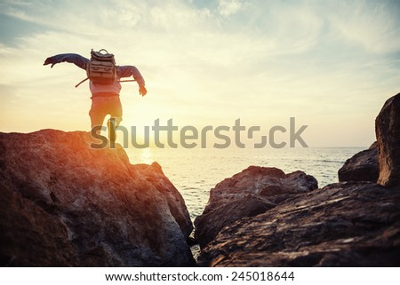 traveler with backpack near sea running to horizon at sunset - stock photo