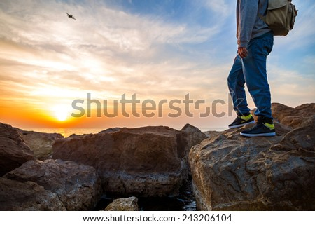 traveler with backpack near the sea looking far away at the horizon at airplane - stock photo