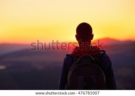 Traveler with backpack watching amazing sunset. Silhouette of the young man on the mountain top. Krkonose mountains, Czech Republic