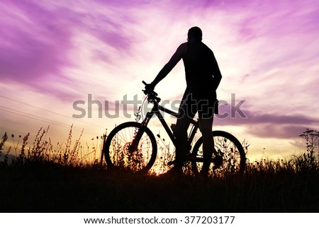 traveler with bike stopped on field at sunset time