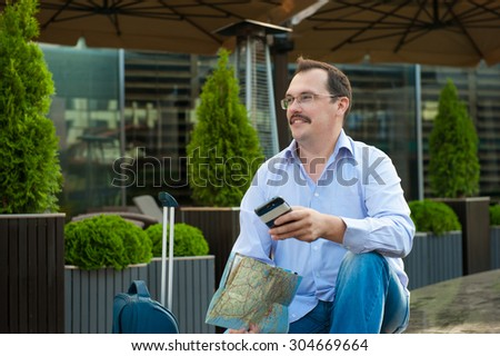 Traveler with mobile phone and city plan sitting outdoors.