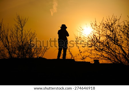 traveler with sunset in dusk, climber silhouette - stock photo