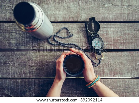Traveler woman holding a cup of tea on wooden table, point of view shot. Thermos and compass on wooden table - stock photo