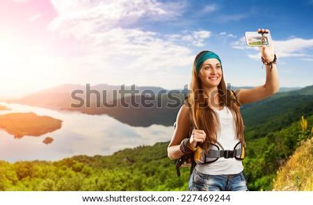Traveler woman is taking selfie outdoor - stock photo