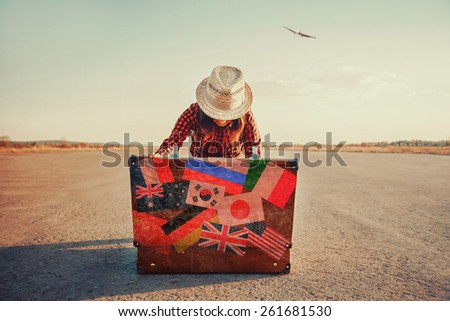Traveler woman looking for something in the open suitcase outdoor. With vintage filter - stock photo