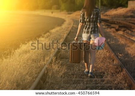 Traveler woman on railway in summer sunset - stock photo