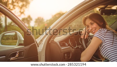 Traveler woman resting on a car wheel during a stop on road trip vacation travel. Young woman relaxing in the car with sunlit backlit road in background.  - stock photo