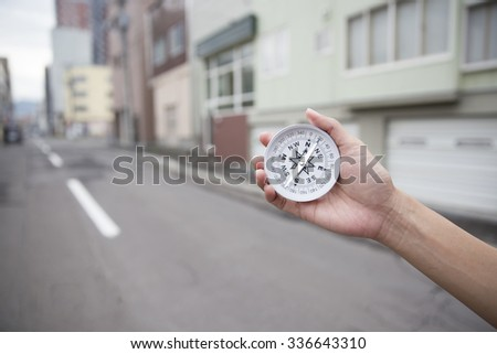 Traveler woman searching direction with a compass - stock photo