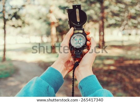 Traveler woman searching direction with a compass in summer forest. Close-up. Point of view shot - stock photo