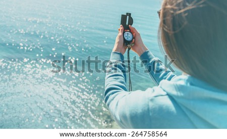 Traveler woman searching direction with a compass on coast near the sea in summer. Rear view - stock photo