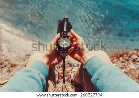 Traveler woman searching direction with a compass on coastline near the sea. Point of view shot - stock photo