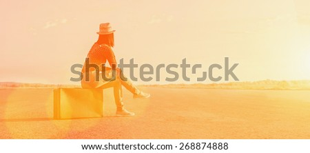 Traveler woman sits on a suitcase and looks away on road. Image with sunlight effect - stock photo