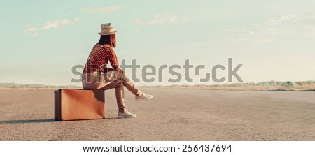 Traveler woman sits on retro suitcase and looks away on road
