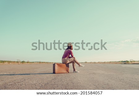 Traveler woman sits on retro suitcase and looks away on road, face is not visible