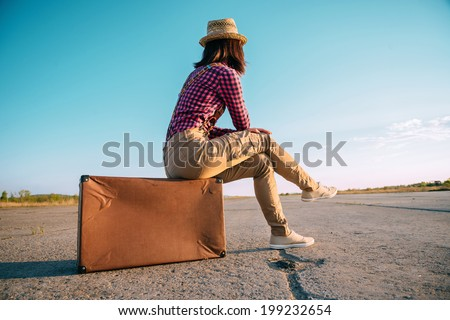 Traveler woman sits on retro suitcase and looks away on road, theme of travel, space for text - stock photo