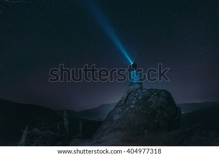 Traveler woman sitting on peak of rock and looking at starry sky, light beam in the night sky. Concept of dream and explore - stock photo