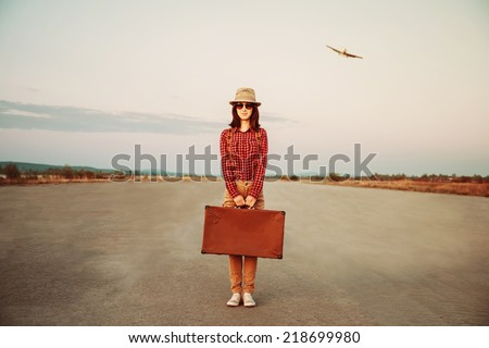 Traveler woman stands on road with vintage suitcase, airplane in sky. Space for text - stock photo
