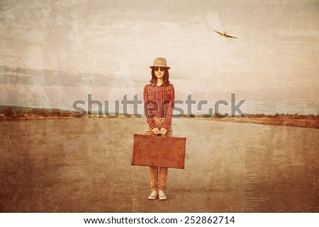 Traveler woman stands on road with vintage suitcase, airplane in sky. Space for text. Vintage image - stock photo