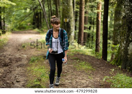 traveler woman walking into a forest with her backpack and looking for something to photograph