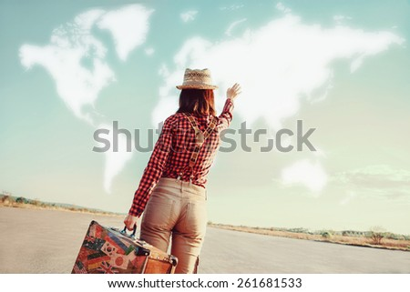 Traveler woman with vintage suitcase waves her hand to map of the world. Concept of travel