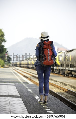 Traveler women walking alone Carrying luggage and waits train on railway station