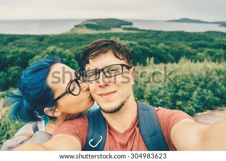 Traveler young loving couple doing selfie on nature in summer. Woman kissing a man