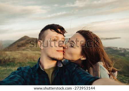 Traveler young loving couple taking self-portrait on peak of mountain. Woman kissing a man with closed eyes - stock photo