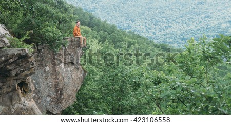 Traveler young man sitting on edge of cliff and enjoying view of nature in summer outdoor - stock photo