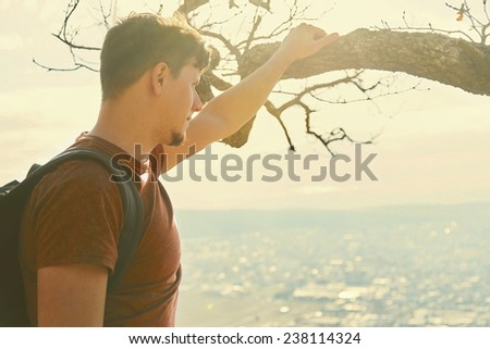 Traveler young man with backpack looking at the city from hill. Concept of tranquil life from the urban bustle. Image with sunlight effect - stock photo