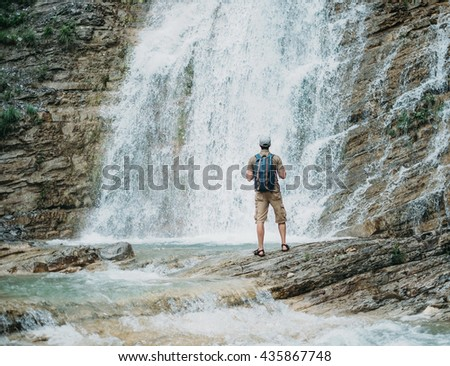 Traveler young man with backpack looking at waterfall in summer outdoor, rear view - stock photo