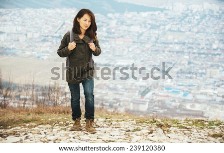 Traveler young smiling woman with backpack walking in highlands over the city. Hiking and recreation theme - stock photo