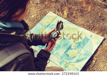 Traveler young woman searching direction with a compass on background of map outdoor. Image with instagram color effect