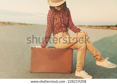 Traveler young woman sitting on suitcase. Low contrast effect - stock photo