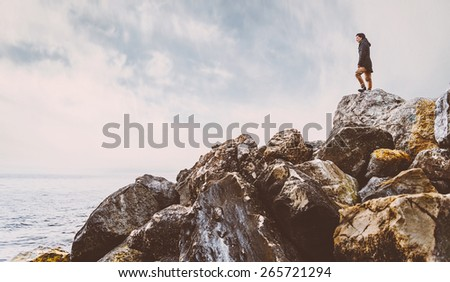 Traveler young woman standing on stone near the sea, side view. Image with instagram filter - stock photo