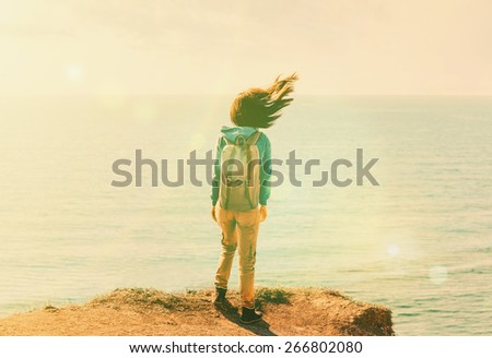 Traveler young woman with backpack standing on coastline near the sea in windy weather, her hair fluttering in the wind. Image with sunlight effect. - stock photo