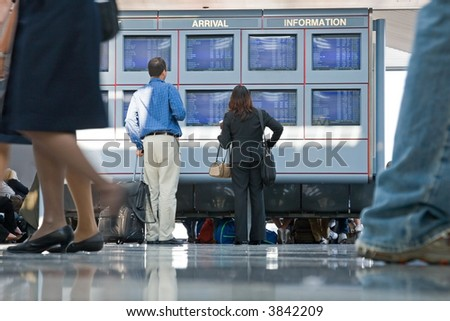 Travelers and businesspeople glance at the departure and arrival information at an airport for airline schedules - stock photo