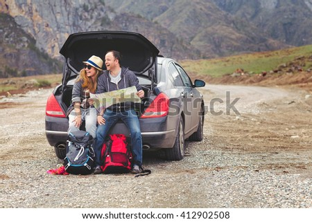 Travelers by car in the mountains in spring see the map - stock photo