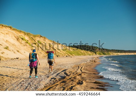 Travelers hiking on the sea beach in summer.