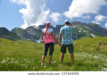 Travelers in an Alpine meadow - stock photo