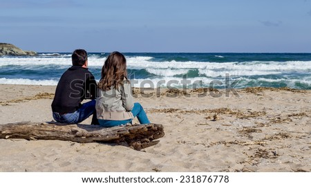 Travelers looking to the horizon on the beach - stock photo