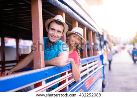 Traveling Asia. Young handsome man with his girlfriend in traditional thai bus. - stock photo