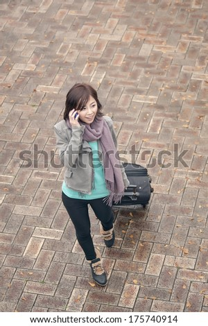 Traveling Asian lady talking on cellphone and holding a luggage in city, Taipei, Taiwan. - stock photo