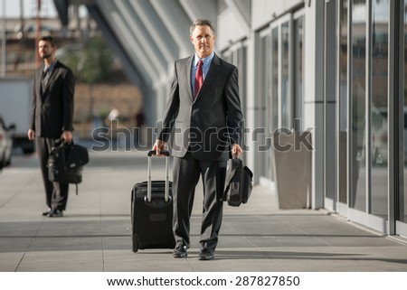 Traveling business man departs at the airport with luggage - stock photo