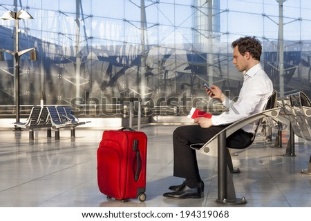 Traveling businessman waiting at lounge with smartphone and luggage - stock photo