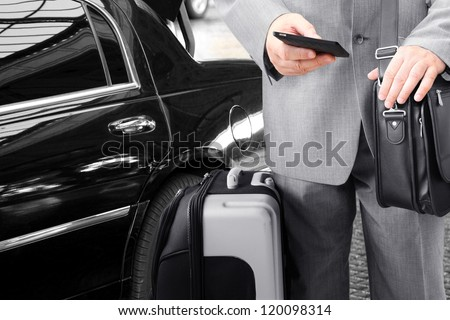 Traveling Businessman with His Luggage Using Phone - stock photo