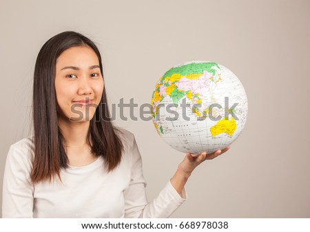 Traveling concept, Asian beautiful woman with globe ball isolated on gray background