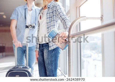 Traveling concept. Happy loving couple in casual wear standing in airport terminal. Focus on hand holding passport with tickets. - stock photo