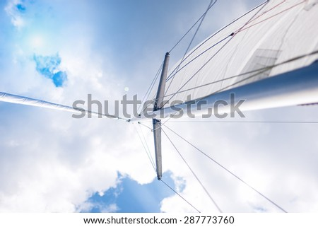 Traveling Concepts: Closeup View of Mid-Size Yacht Mast and Canvas Sail Shot Against Bright Summer Sun. Horizontal Image Orientation - stock photo