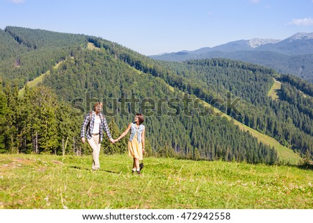 Traveling couple walking together at the summer meadow and looking around mountain view